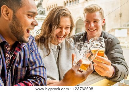 multi-racial friends drinking beer and laughing and having fun sitting at the table in an outdoor restaurant - concept of friendship between different cultures