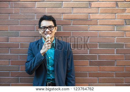 Smiling young asian man in his twenties enjoying ice cream while standing near brick wall outside on a break