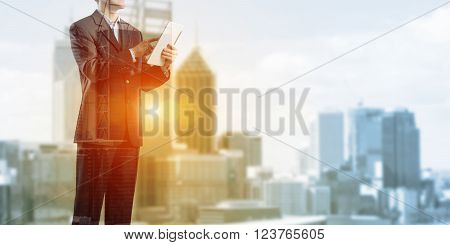 Exposure of city and businessman using tablet device as development concept