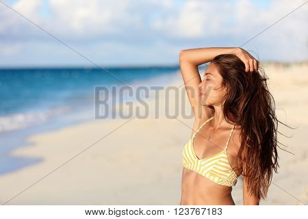 poster of Carefree bikini woman enjoying sunset on beach. Beautiful relaxing Asian model caressing hair with c