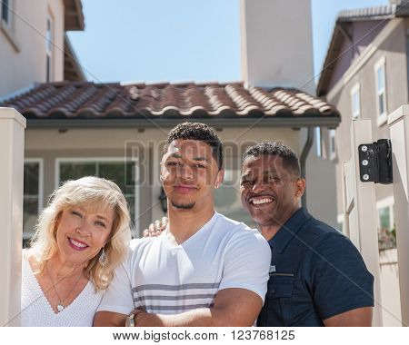 Closer view of multiracial family posing in yard featuring son.