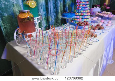 Candy bar on gender reveal party. Lemonade in a large glass jar on a party. Empty glasses for drinks with a straw.