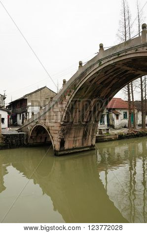 Fu Liang Qiao Bridge and old buildings in traditional Asian architecture lining a dirty water canal in Sijing Ancient town located in Songjiang district of Shanghai China.