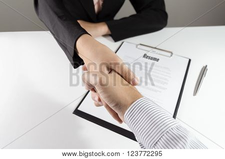 Businessman and businesswoman handshake over the resume document.