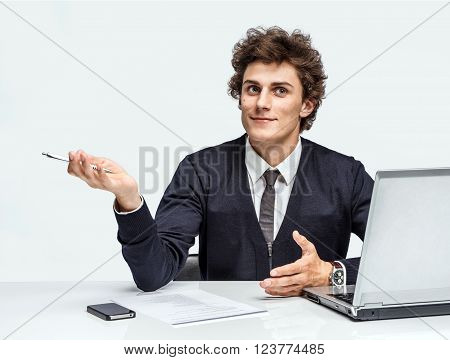 Young student thinking while writing notes. Man at the workplace working with computer on gray background.