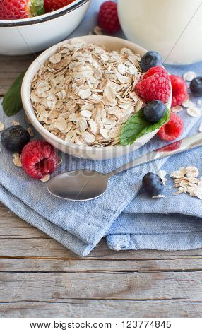 Rolled oats in a bowl with berries and milk on the wooden table