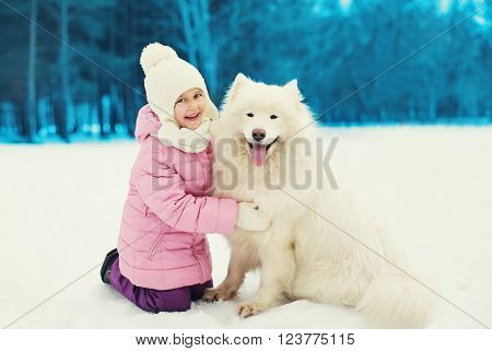 Happy smiling child playing with white Samoyed dog on snow in winter day