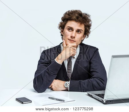 Take thought. Young Businessman at the workplace working with computer on gray background.