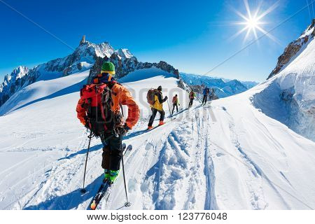 A group of skiers start the descent of Valle Blanche, the most famous offpist run in the Alps, Valle Blanche descent links Italy and France through the Mont Blanc Massif. Chamonix, France, Europe.