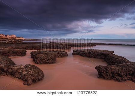 Drama sunset at sea. Beach wave Gale blurred.