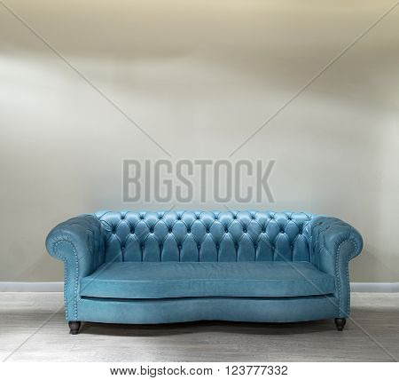 House interior with blue leather sofa on a blank wall.