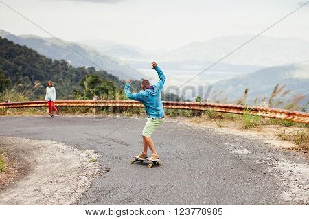 hipster man longboarding extremely in tropcis vacation
