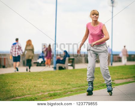 Young Female Exercise Outdoor On Rollerblades.