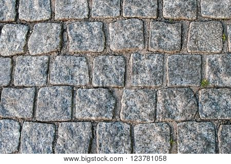 The ancient paving blocks of marble. Texture of antique marble. The ancient cobbled street. Paving stones of historic European streets. The texture and the background paving.