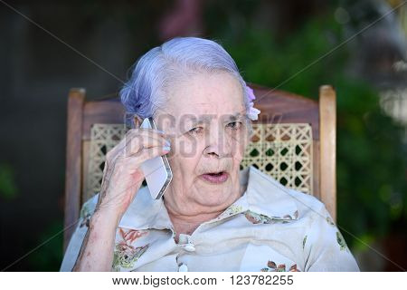 grandma talking with white modern smartphone in park