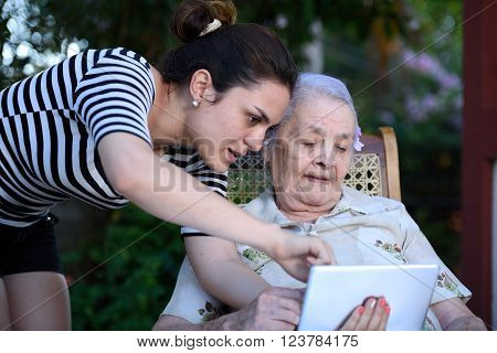 grandma studing communication tablet device with girl