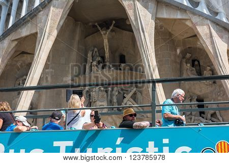 SPAIN, BARCELONA - SEPTEMBER 13: People sitting on a double decker tourist coach in front of The Sagrada Familia Cathedral in Barcelona on September 13, 2015