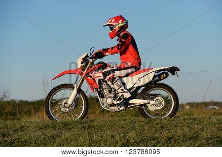 Man with protection riding motocross motorcycle on terrain
