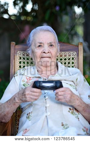 grandma holding joystick and playing games outside