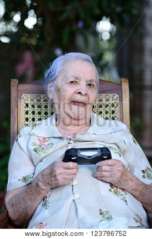 smiling grandma play videogames with wireless joystick