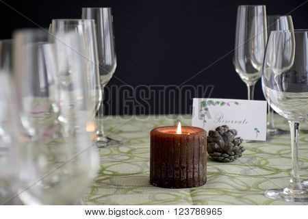 the place at the table with the placeholder and the candle lit.