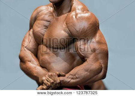 Muscular man's side chest pose. Bodybuilder posing on blue background. Close-up of ripped muscles. Dieting is the key.