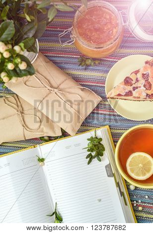 cherry pie tea glass jar of honey and other decorations on the colorful tablecloth. sunlight