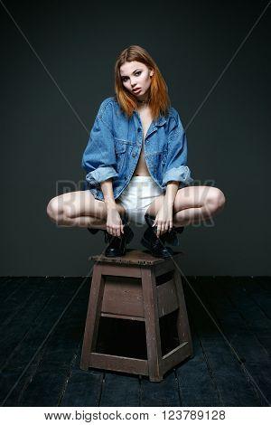 Young beautiful woman wearing denim jacket posing in boots
