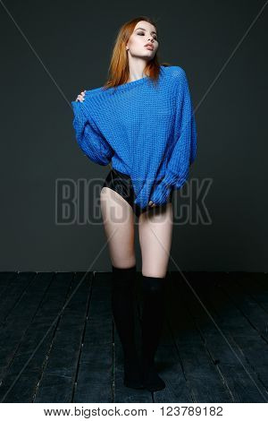 Young beautiful woman posing in blue knitted sweater