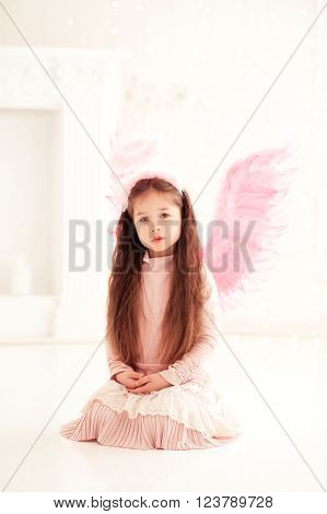 Cute baby girl 4-5 year old wearing wings and pink dress. Looking at camera. Childhood.