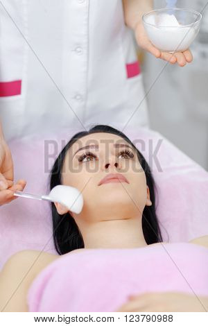 Young beautiful woman with dark hair gets procedure in the beauty salon. Face Skin Care. Cleansing Procedure. Cosmetology.