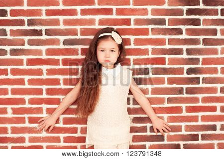 Stylish kid girl 5-6 year old posing over brick wall looking at camera. Childhood.