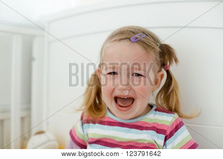 Crying little toddler, having a tantrum during a terrible two phase, raging in her crib. Childhood, growing up, developmental phase and parent patience concept.