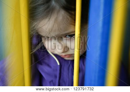 Thoughtful and sad little girl hiding behind fence feeling blue and distressed. Childhood growing up neglection disappointment loneliness and sadness concept.