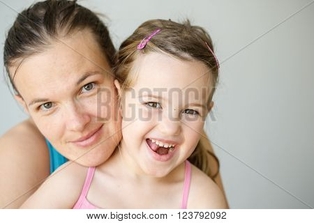 Mother and daughter embracing smiling being affectionate happy and loving. Parenthood childhood happiness and family life concept. Grey seamless background.