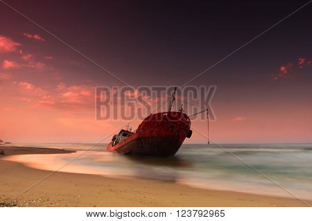Ship after wreck on the coast colorful sunset