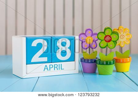 April 28th. Tax Day. Image of april 28 wooden color calendar on white background with flowers. Spring day, empty space for text.