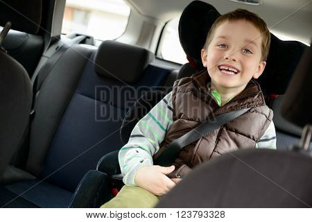 Happy little boy in car safety seat. Children car safety concept