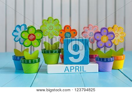April 9th. Image of april 9 wooden color calendar on white background with flowers. Spring day, empty space for text.