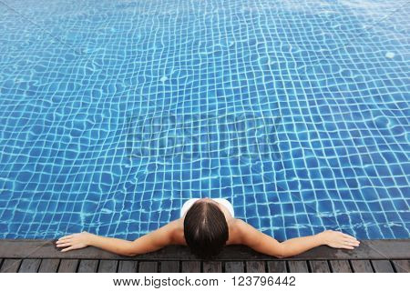 Woman on vacation sitting in swimming pool