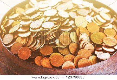 Selective focused coins in old monk's alms-bowl with soft mood color tone