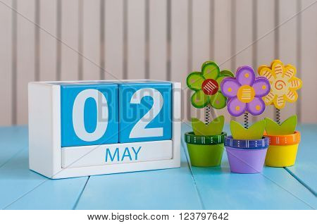 May 2nd. Image of may 2 wooden color calendar on white background with flowers. Spring day, empty space for text.  last spring month.
