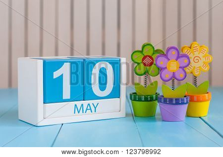 May 10th. Image of may 10 wooden color calendar on white background with flowers. Spring day, empty space for text.  International or World Press Freedom Day.