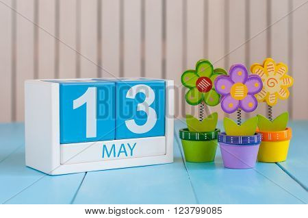 May 13th. Image of may 13 wooden color calendar on white background with flower. Spring day, empty space for text.