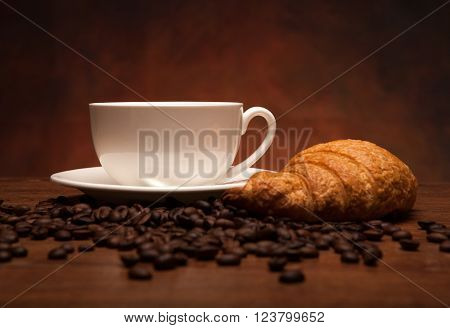 cup of coffee and croissants on the coffee background
