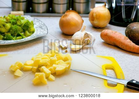 cooking vegetarian soup of chickpeas and broccoli. knife, broccoli. carrot,  onion and potato on a board