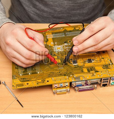 Repairer Is Looking For The Fault Of The Motherboard With A Multimeter.