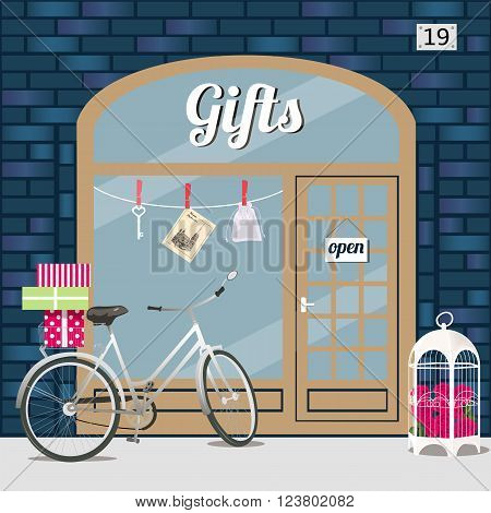 Gifts shop's facade of blue brick. Bike with gift boxes in basket and birdcage with roses at the fore . Key, sashe and postcard in the window. Vector illustration eps 10.