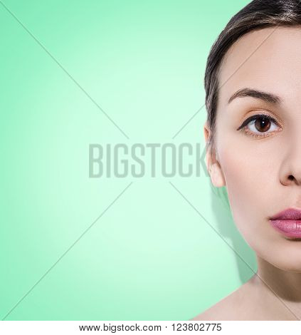 Half-faced woman on green background. Concentrated face.