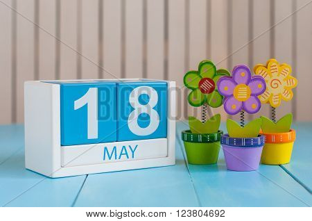 May 18th. Image of may 18 wooden color calendar on white background with flowers. Spring day, empty space for text.  International Museum Day.